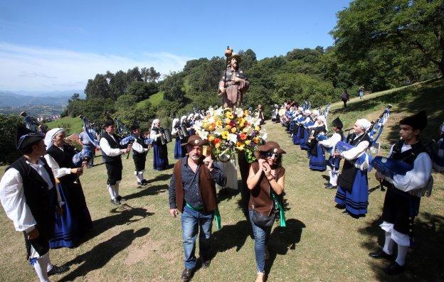 La imagen de Santiago Apóstoldurante la procesión, con la Real Banda de Gaitas Ciudad de Oviedo.
