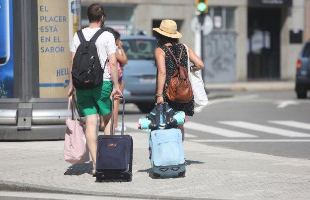 Una pareja de turistas camina con sus maletas por una calle de Gijón.