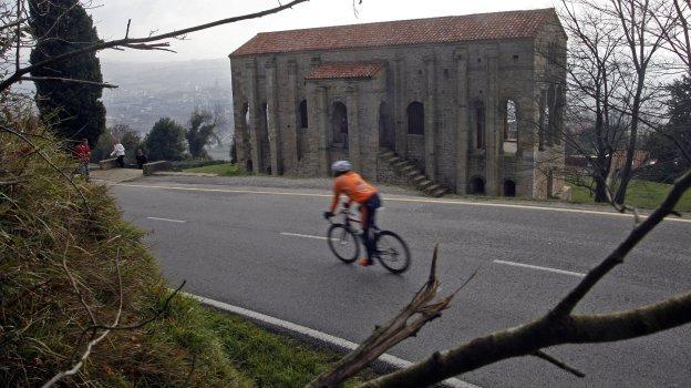 Un ciclista circula por la carretera aneja a Santa María del Naranco.
