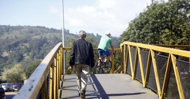 Dos vecinos cruzan por la pasarela sobre las vías del tren .