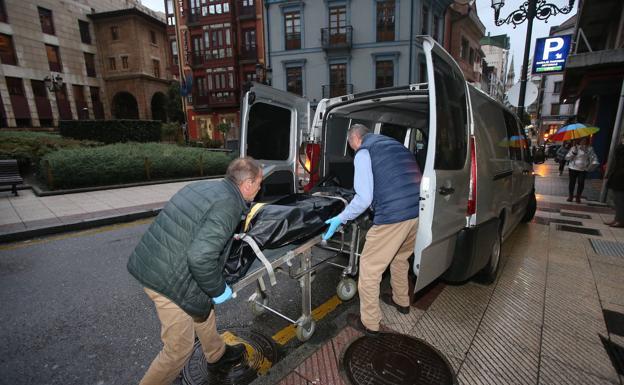 Personal de una funeraria sacan uno de los cuerpos encontrados en un piso de Oviedo./Álex Piña